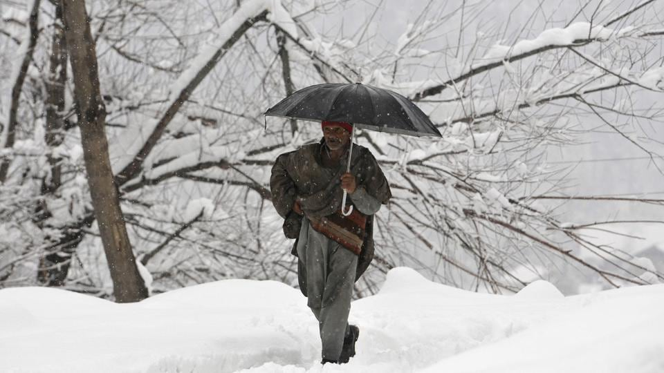 A man walks through a snow-covered road during fresh snowfall at Tangmarg road about 38 kilometers from Srinagar, Jammu and Kashmir, on Wednesday, January 2, 2019.