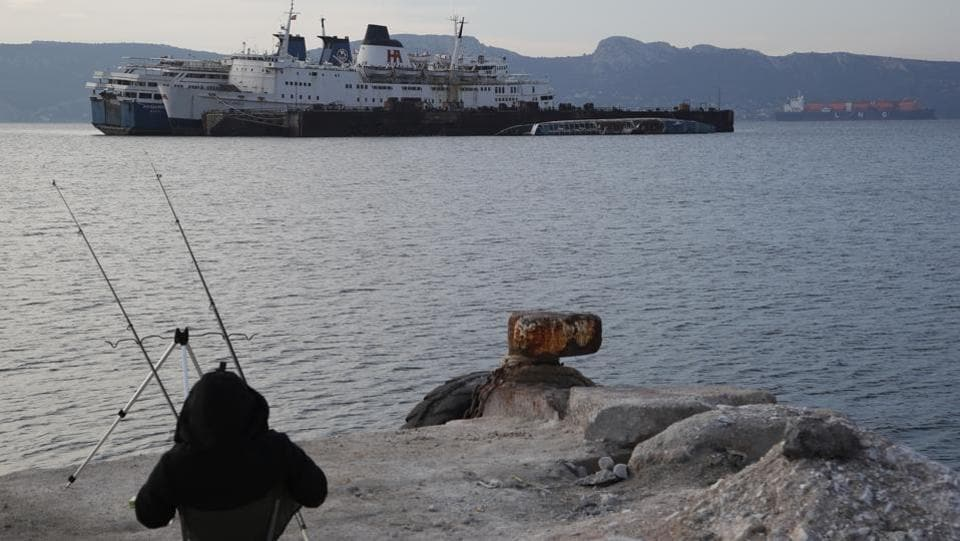 "A man fishes as half sunken and abandoned ships are moored in the Gulf of Elefsina. ""It is the sins of many years which we now have come (to solve),"" said Gargaretas. ""We are trying in a very short period of time and with huge bureaucratic and legal hurdles to remove all these ships from the area."" (Thanassis Stavrakis / AP)"