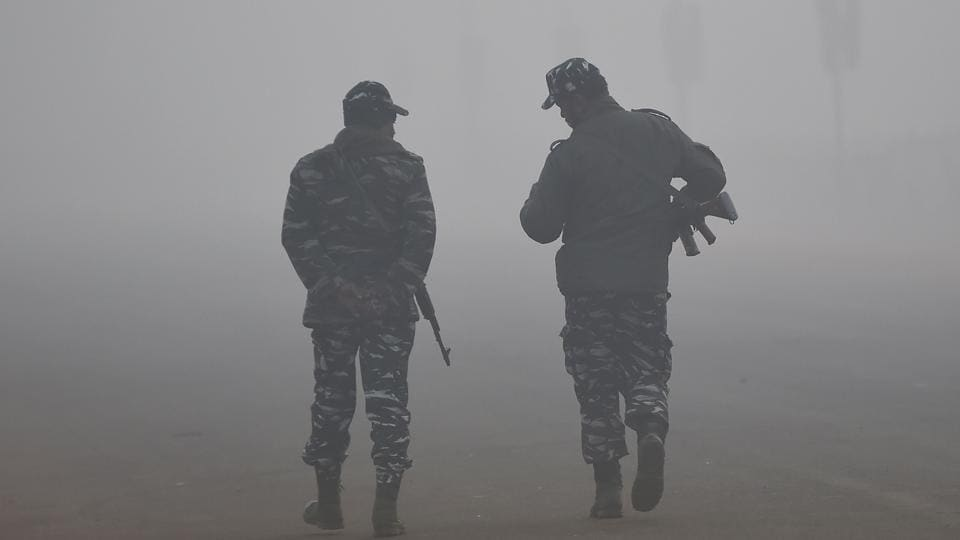 Security personnel walk amid heavy fog and smog conditions in New Delhi on January 3, 2019.