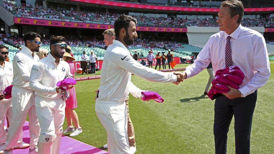 India's Cheteshwar Pujara, second right, presents to former Australia player Glenn McGrath, right, a pink cricket cap.