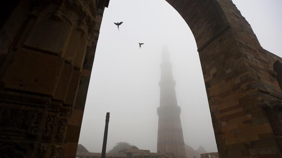 A view of the Qutub Minar shrouded in fog on a cold winter morning at Mehrauli in New Delhi. (Amal KS / HT Photo)