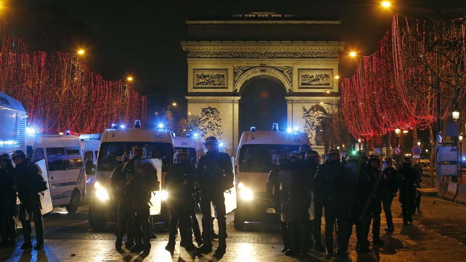 Riot police officers take position at the Champs Elysees avenue during a yellow vest protest in Paris on Saturday.