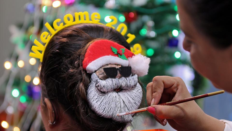 A make-up artist decorates the hair of a woman in the shape of Santa Claus during the New Year preparations in Ahmedabad, Gujarat. (Amit Dave / REUTERS)