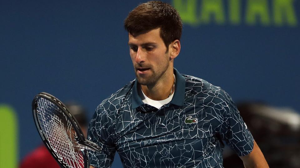 Novak Djokovic of Serbia reacts as he holds his broken racquet during his Qatar Open semi-final match.
