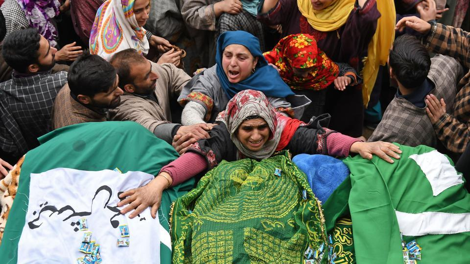 A Kashmiri woman touches the feet of two slain militants during a funeral procession in Chursoo Awantipora, in Pulwama district south of Srinagar, Jammu and Kashmir. (Tauseef Mustafa / AFP)