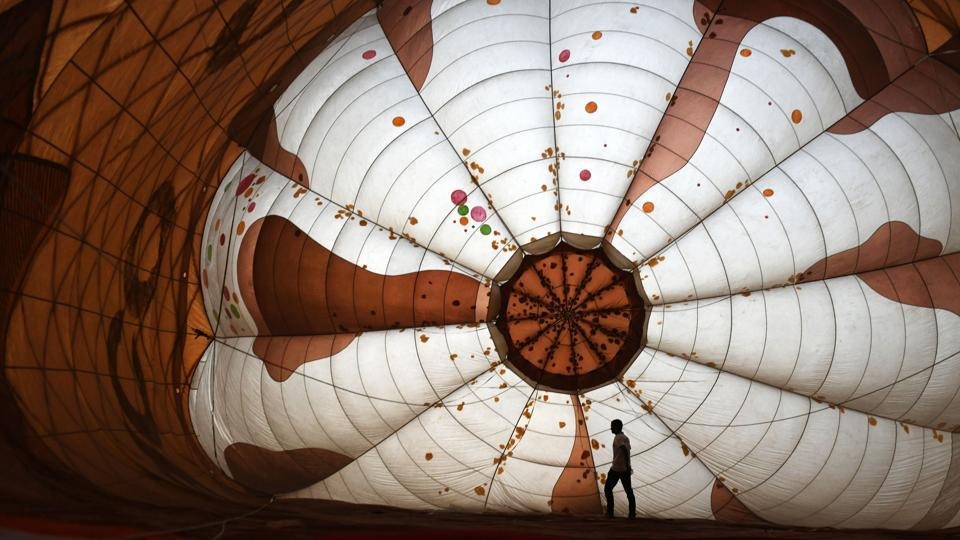 A pilot stretches a hot balloon air as it inflates during the inauguration ceremony of the 5th edition of Tamil Nadu International Balloon Festival in Chennai, Tamil Nadu. (Arun Sankar / AFP)
