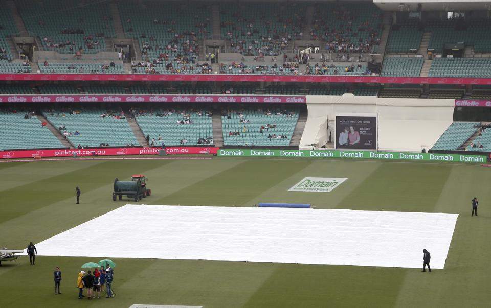 Rain falls as the pitch is covered during a delay before play on day 5 of the cricket test match between India and Australia in Sydney, Monday, Jan. 7, 2019. (AP Photo/Rick Rycroft) (AP)