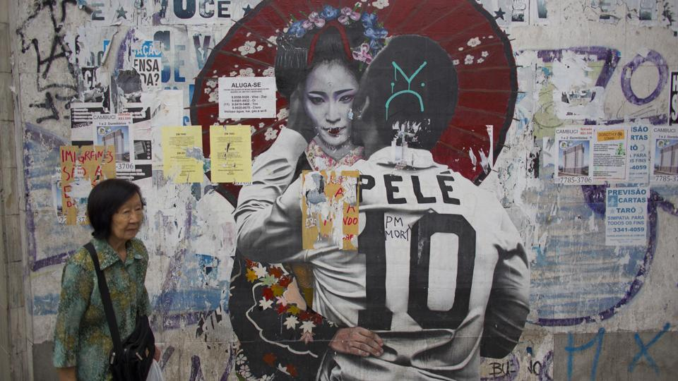 A woman walks by a mural of soccer legend Pele hugging a Geisha in Sao Paulo. Brazil's first Japanese migrants arrived aboard the steamship Kasato Maru on June 18, 1908, spurring a wave that grew to about 2 million people. They introduced foods that changed Brazilian cuisine and farming techniques that helped turn Latin America's biggest country into an agricultural superpower. (Victor R. Caivano / AP)