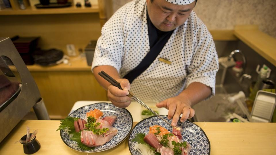 "While slicing fish at a restaurant, sushi chef Hiro Konno said: ""I don't think we should disconnect so much (from Japanese culture). Those of us who have Japanese roots should do more to preserve them. For me, the closing of the newspaper is very sad."" (Victor R. Caivano / AP)"