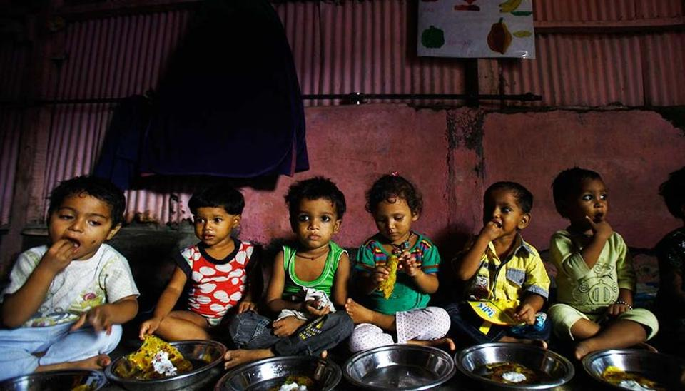 Malnourished children eat a meal at the Apanalaya centre, an organisation working for the betterment of slum children, Mumbai.