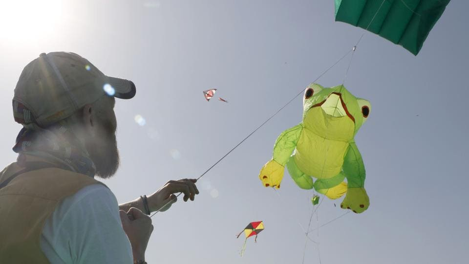 A kite flier hoists a frog shaped kite during the festival. Around 151 participants including nationals of the United States, United Kingdom, Cambodia and Nepal have arrived to participate in this event. (Siddharaj Solanki / HT Photo)