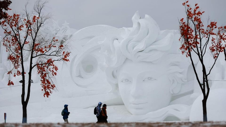 People walk past a snow sculpture in Harbin. Highlights include sled rides on the Songhua river, mass weddings, and towering sculptures of ice and snow carved by thousands of artists and workers.  (AFP)