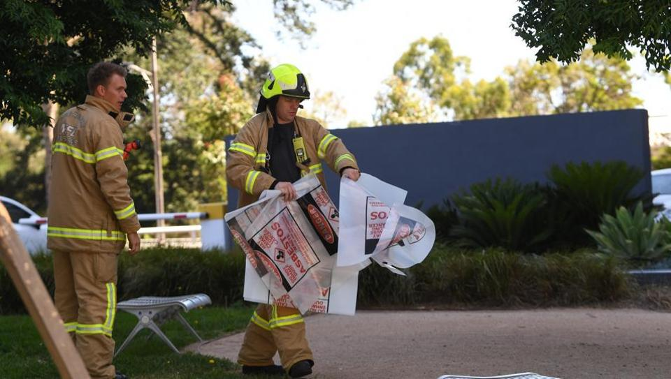 A fire fighter is seen carrying a hazardous material bag into the Korean consulate in Melbourne on Wednesday.