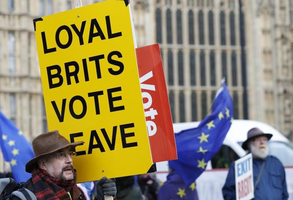 A vote leave pro-Brexit demonstrator holds a placard with anti Brexit protesters in the background as they voice their opinions outside the Palace of Westminster, in London, Wednesday, Jan. 9, 2019. The British government was bringing Prime Minister Theresa May's Brexit deal back to Parliament for possible approval next week, although many lawmakers are expected to vote against the deal. (AP Photo/Alastair Grant)