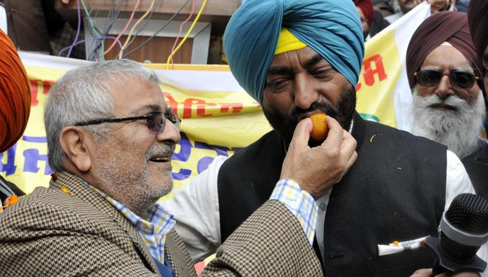 Suspended AAP Patiala MP Dr Dharamvira Gandhi offers sweets to Sukhpal Singh Khaira during the launch of Punjabi Ekta Party in Chandigarh on Tuesday.