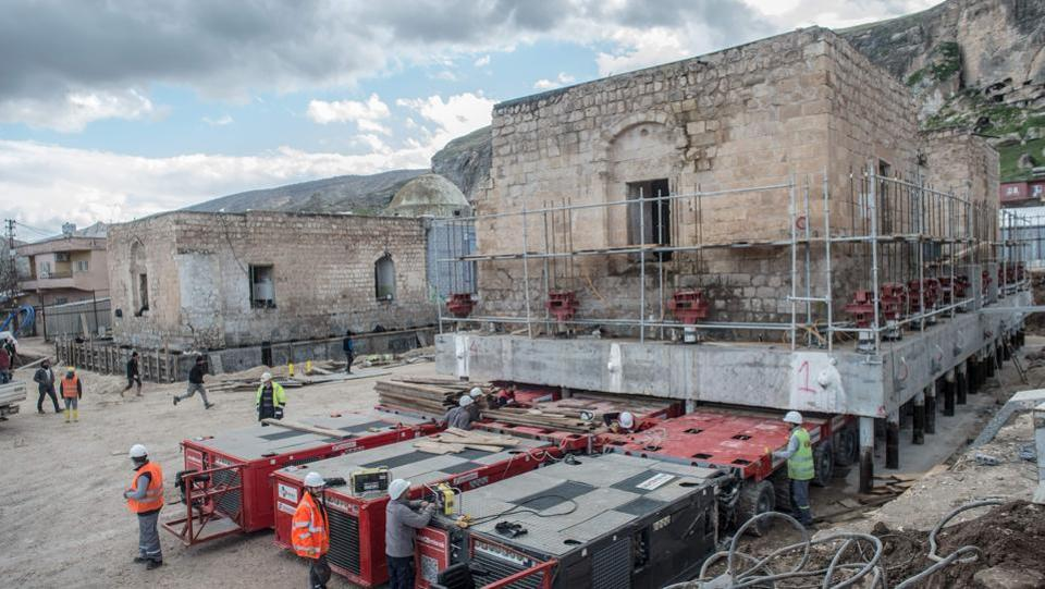 "In one lengthy operation last August, the 1,600-tonne Artuklu Hamam bath house was loaded onto a wheeled platform and moved down a special road to its new home. Workers also recently moved the remnants of a 14th-century Ayyubid mosque (pictured), transporting it three kilometres to a site that will become a ""cultural park"". Such relocations have turned Hasankeyf into a construction site. (Bulent Kilic / AFP)"