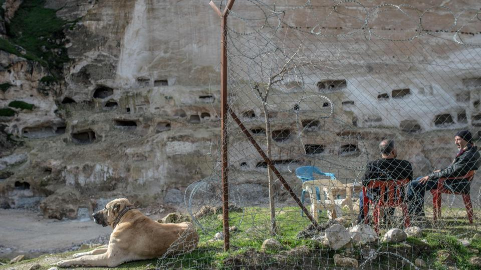 Residents sit in front of historical caves in Hasankeyf. Assyrians, Romans, Seljuks... the empires that washed over this region have left an exceptional heritage, not least the thousands of caves that were inhabited as recently as the 1970s and are a major tourist draw. The government dismisses criticism, arguing that everything has been done to save the monuments. (Bulent Kilic / AFP)