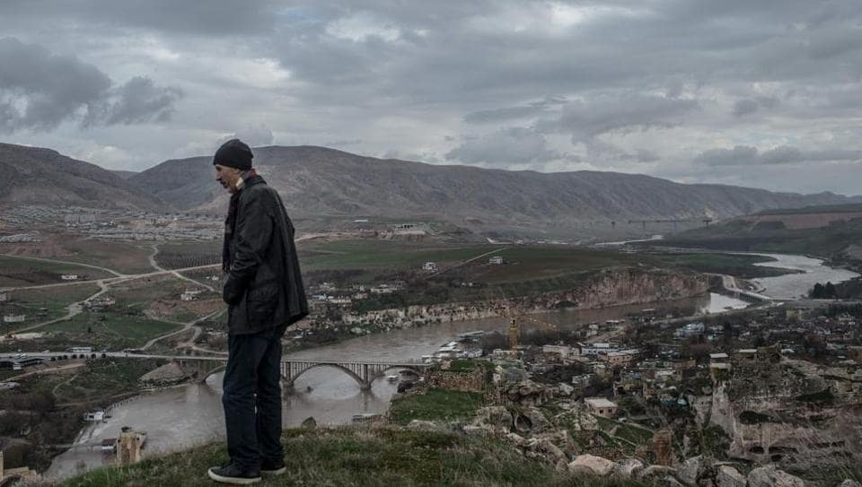 "From the ancient citadel overlooking the valley, Ridvan Ayhan looks at the Tigris with a furrowed brow. The river that supported his family's town for generations will soon destroy it. ""My grandchildren will not see where I grew up, where I lived. They will ask me, 'Grandpa, where do you come from? Where did you live?' What will I do? Show them the lake?"" asks Ayhan, readjusting the scarf over his face. (Bulent Kilic / AFP)"