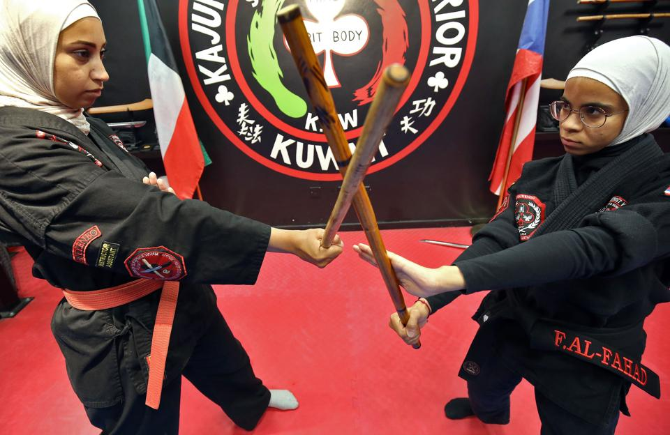 Asma Hasnawi (L) and Fai al-Fahad, Kajukenbo assistant-master, practise in Kuwait City. Hasnawi and her daughter Riham spend more than 12 hours a week learning kajukenbo, a mixed martial art the mother says boosts her child's confidence and thwarts bullying. The sport's name was derived from the various forms of martial arts it includes: karate (KA), judo and jujitsu (JU), kenpo (KEN) and boxing (BO). (Yasser Al-Zayyat / AFP)