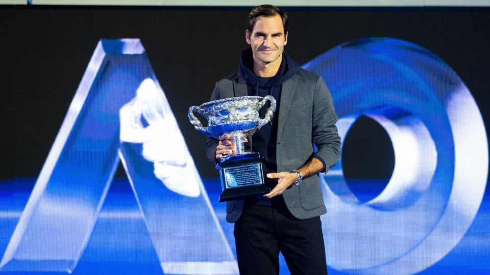 Roger Federer poses with the men's singles trophy during the draw for the Australian Open.