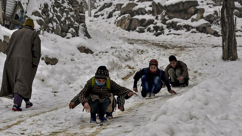 Children play on a snow-covered unpaved road, on the outskirts of Srinagar, Wednesday, Jan. 9, 2019.
