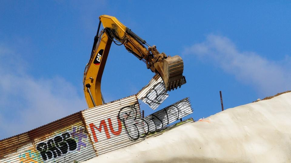 US workers use machinery to replace the metal sheets of the border fence between the United States and Mexico, as seen from Tijuana, Mexico. (Jorge Duenes / REUTERS)