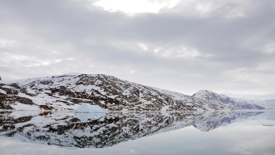 "The snow-covered shore is reflected in the still water of a fjord near Tasiilaq. Despite the new challenges brought by the changing climate, Greenland's residents are known for their resilience. ""The beauty is that Greenlanders have always been good at adapting, so they will survive anyway, whatever will happen,"" Moeller said. (Lucas Jackson / REUTERS)"