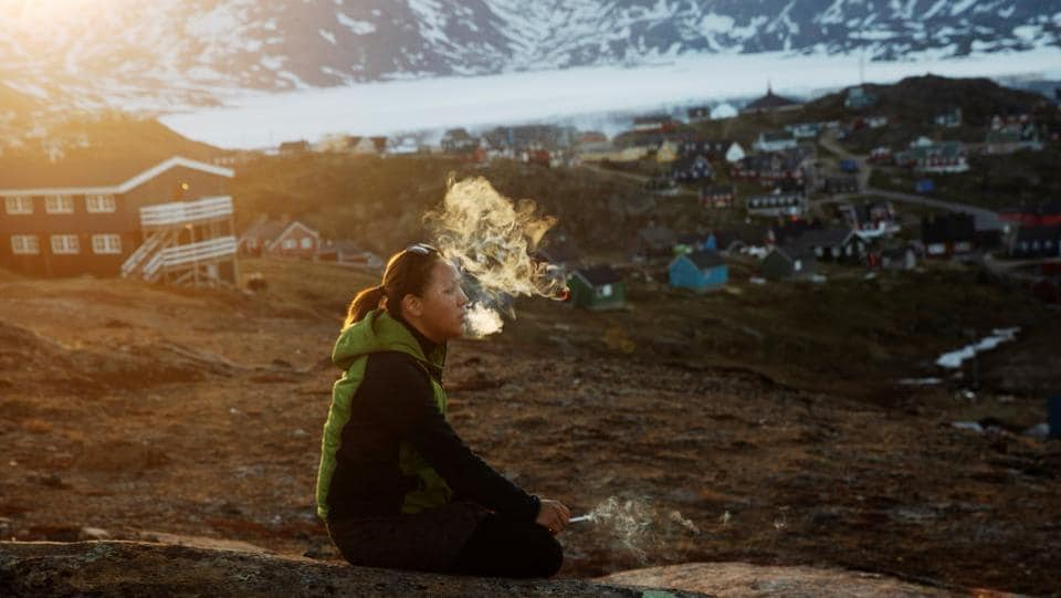 "A young girl sits on a stone and smokes in the late evening sunshine above Tasiilaq. Moeller also cited another temporary advantage climate change has brought to his tourism business: People want to see the ice cap before it is too late. ""Go and see the glaciers before they disappear. That's the thing you hear again and again,"" he said. (Lucas Jackson / REUTERS)"