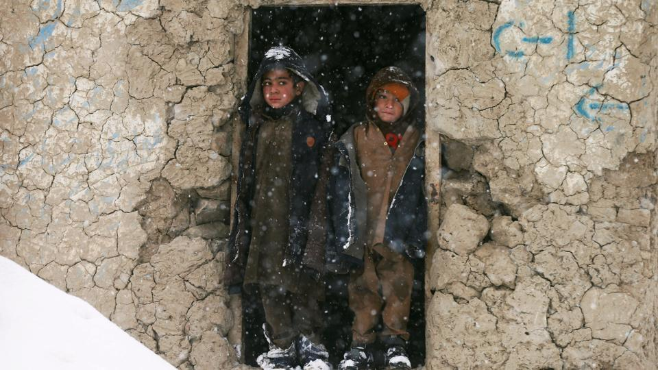 Internally displaced Afghan boys stand outside their shelter during snowfall in Kabul, Afghanistan. (Mohammad Ismail / REUTERS)