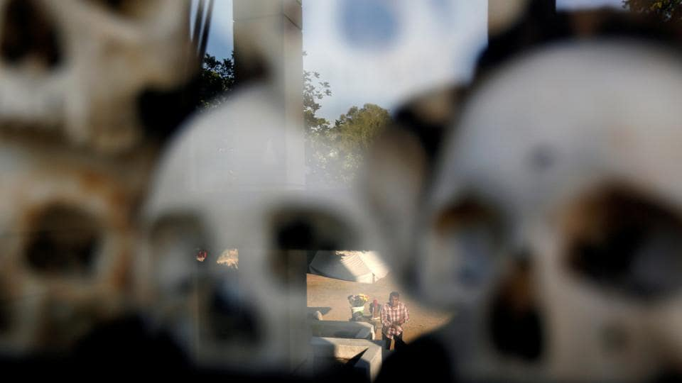 "Skulls and bones are displayed as a man is reflected in a glass pane, at the Choeung Ek memorial of more than 8,000 victims of the Khmer Rouge regime, at a ""killing fields"" site located on the outskirts of Phnom Penh, Cambodia. (Samrang Pring / REUTERS)"