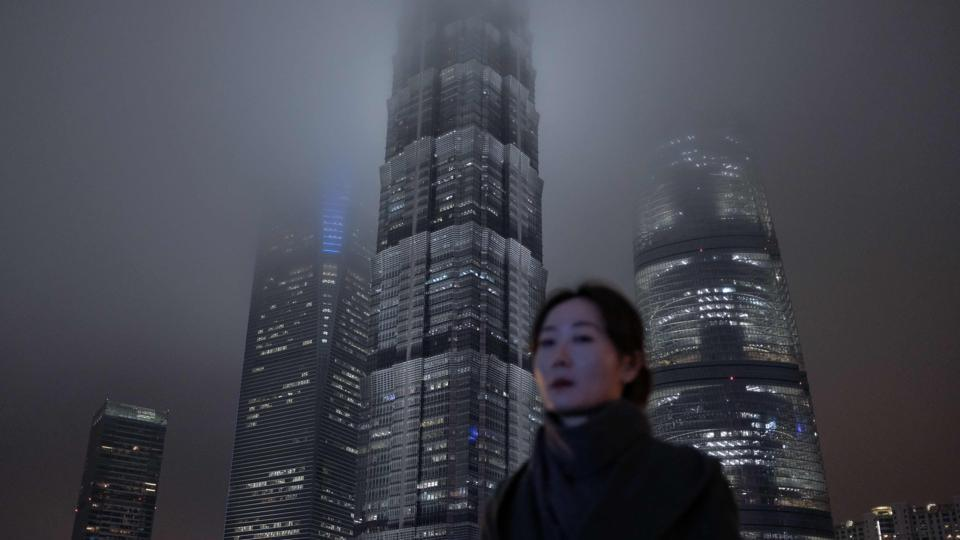 TOPSHOT - In this photo taken on January 10, 2019, a woman walks on a pedestrian bridge in Shanghai's Lujiazui financial district. (Photo by MATTHEW KNIGHT / AFP)