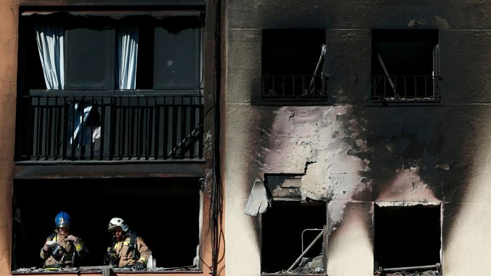 Firefighters check the damage after extinguishing a fire that broke out at an apartment building in Badalona near Barcelona. At least three people were killed and several others, including a baby, were injured. (Pau Barrena / AFP)