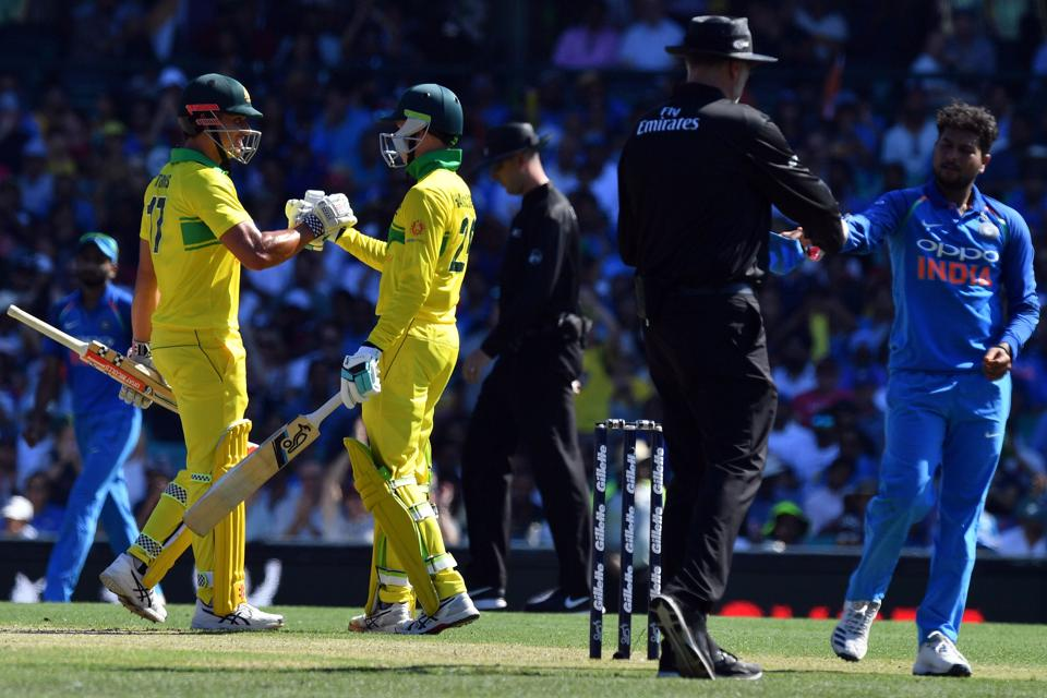Australia's batsman Peter Handscomb (C) celebrates reaching his half century (50 runs) with a teammate Marcus Stoinis during the first one-day International (ODI) match between Australia and India at the Sydney Cricket Ground. (AFP)