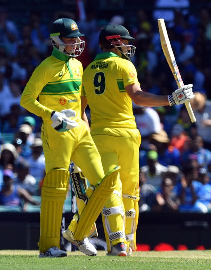 Australia's batsman Shaun Marsh (R) celebrates reaching his half century (50 runs) as his teammate Australia's Peter Handscomb looks on during the first one-day International (ODI) match between Australia and India at the Sydney Cricket Ground. (AFP)