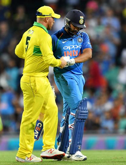 Australia's captain Aaron Finch (L) shakes hands with India's batsman Rohit Sharma after his dismissal during the first one-day international (ODI) match between Australia and India at the Sydney Cricket Ground (AFP)