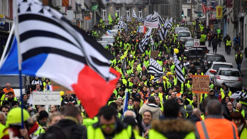 Yellow Vest protesters wave French and Brittany flags during an anti-government demonstration called by the Yellow Vest movement in Saint-Brieuc, western France, on January 12, 2019.
