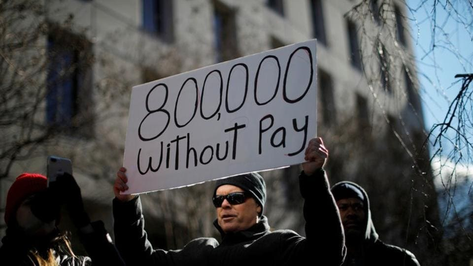 """A demonstrator holds a sign, signifying hundreds of thousands of federal employees who won't be receiving their paychecks as a result of the partial government shutdown, during a """"Rally to End the Shutdown"""" in Washington, U.S., Jan. 10, 2019 (File Photo)"""