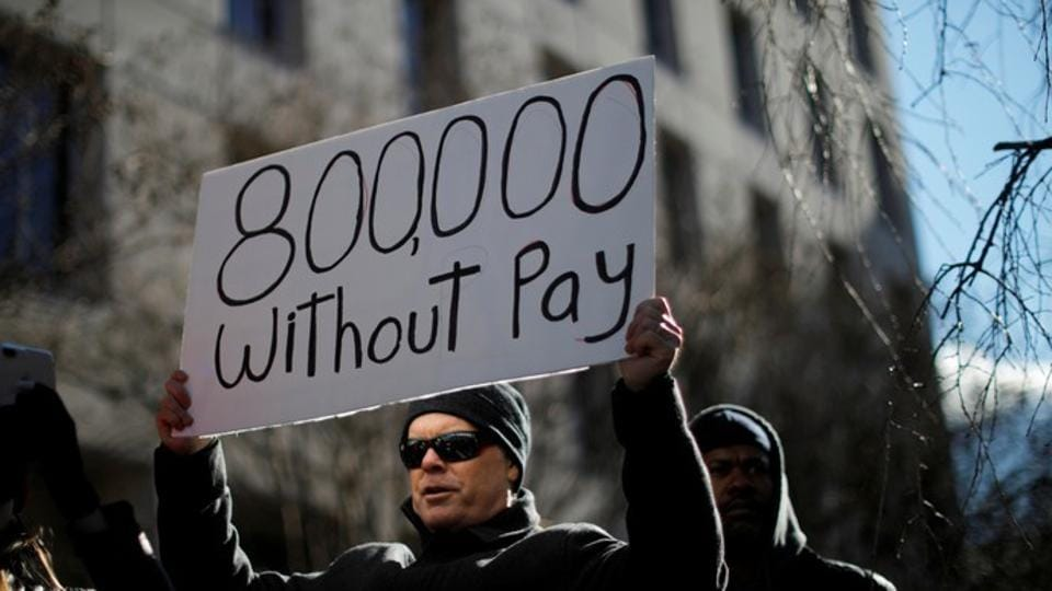 A demonstrator holds a sign, signifying hundreds of thousands of federal employees who won't be receiving their paychecks as a result of the partial government shutdown, during a 'Rally to End the Shutdown' in Washington, US.