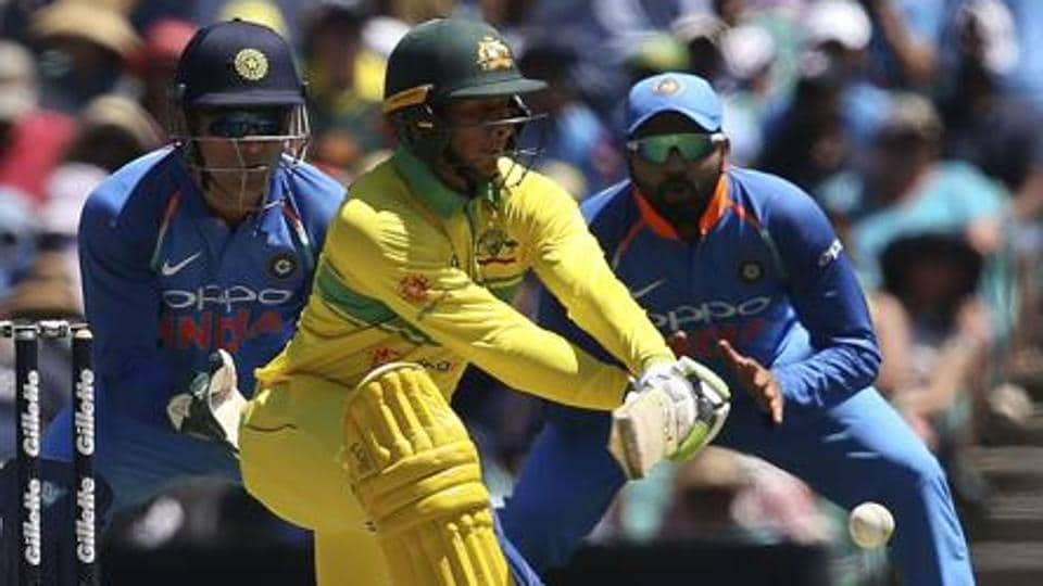 Australia's Usman Khawaja, center, plays a reverse sweep against India during their one day international cricket match in Sydney.