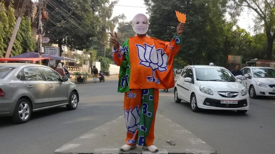 A BJPsupporter wears a mask depicting Prime Minister Narendra Modi, and drapes himself with flags of BJP's symbol at a traffic signal in Bhopal.