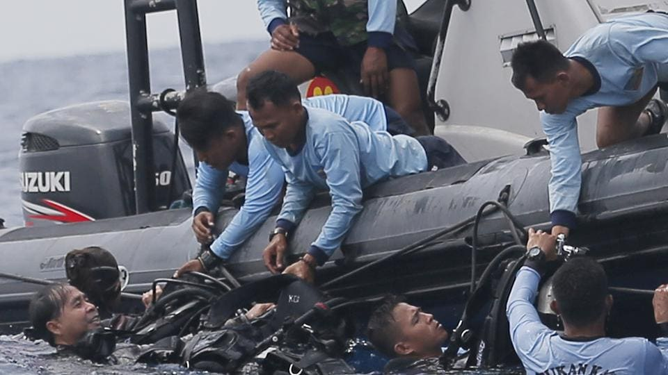 Indonesian navy frogmen emerge from the water during a search operation for the victims of the crashed Lion Air plane.
