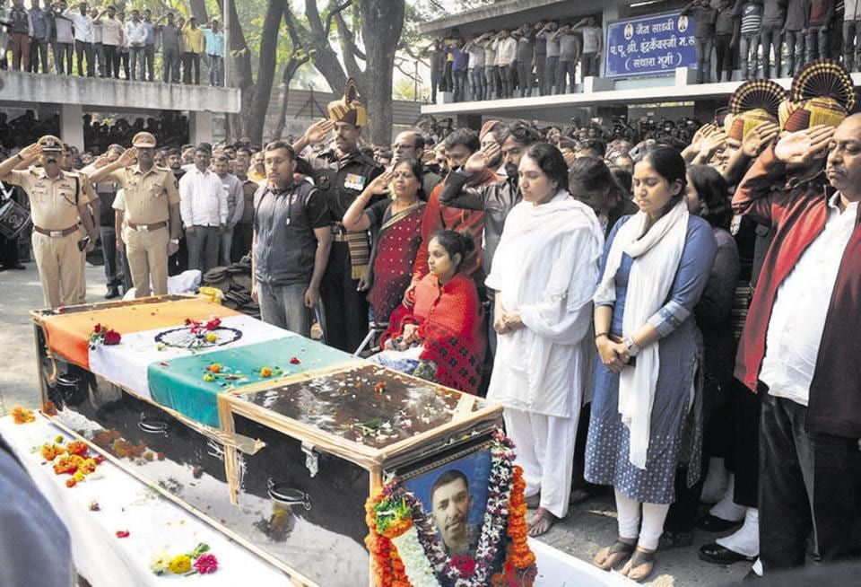 Major Shashidharan V Nair, who was killed in an IED explosion in Rajouri, J&K last week, was laid to rest with a 21 gun-salute and full military honours at the Vaikunth crematorium on Sunday. The pyre was lit at 11.30 am in the presence of Major Nair's family (foreground). Also present were district guardian minister Girish Bapat and MP Anil Shirole.