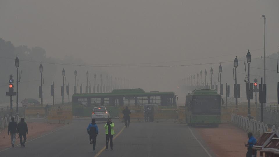 People walk near Raisina Hills on a cold, foggy morning, in New Delhi, Sunday, Jan 13, 2019.