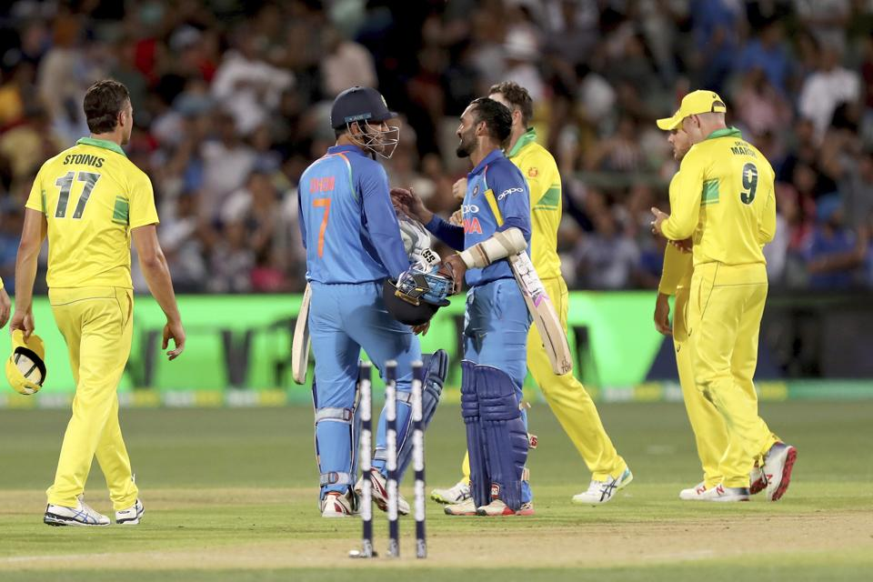 India's M.S. Dhoni (7) and teammate Dinesh Karthik celebrate their win over Australia during their one day international cricket match in Adelaide. (AP)