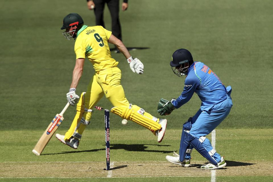 India's M.S. Dhoni, right, attempts a runout of Australia's Shaun Marsh during their one day international cricket match in Adelaide. (AP)