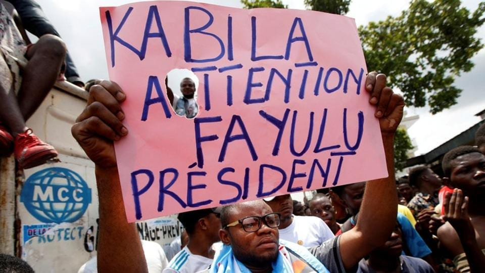 Supporters of the runner-up in Democratic Republic of Congo's presidential election, Martin Fayulu hold a sign before a political rally in Kinshasa, Democratic Republic of Congo on January 11.