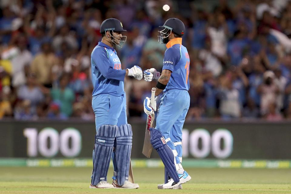 India's Virhat Kohli celebrates his 100 against Australia with teammate M.S. Dhoni during their one day international cricket match in Adelaide. (AP)
