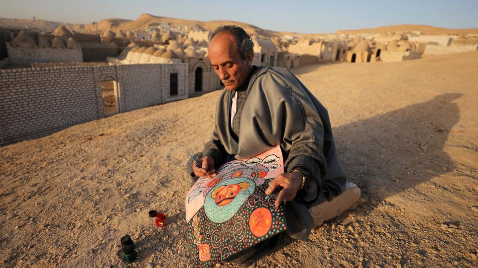 Egyptian artist Hassan el-Shark paints a piece of art with his own handcrafted colours near the 'City of the Dead' in Minya Governorate, Upper Egypt. El-Shark's paintings of village life, created from the mud, grass and leaves he finds around him, are treasured in Egypt for keeping a traditional skill alive. (Mohamed Abd El Ghany / REUTERS)