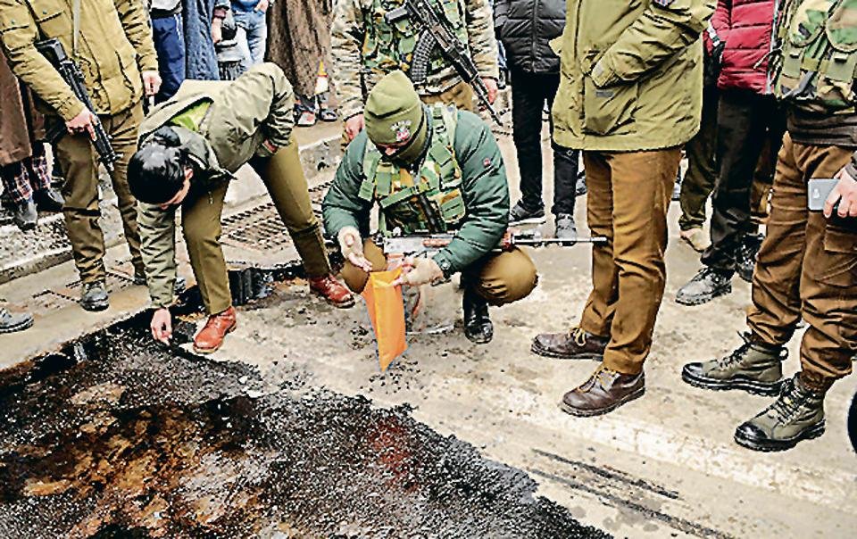 Police officers inspect the site of a grenade explosion, at Lal Chowk, in Srinagar, on Friday.