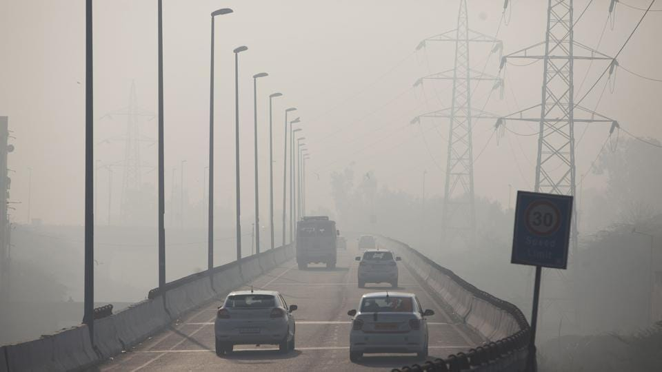 Indian commuters drive amidst heavy smog along a road in New Delhi on January 17, 2019.
